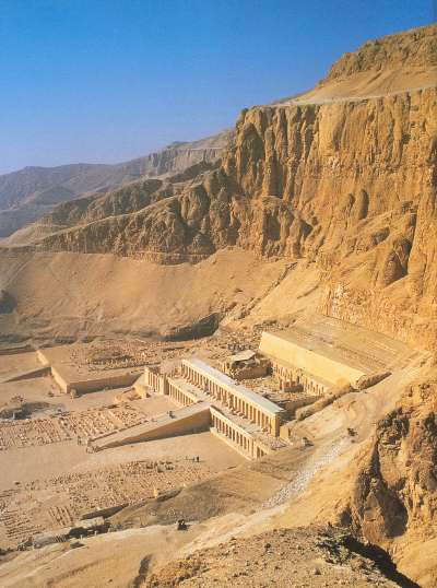 The agricultural Nile floodplain gives way abruptly to deserts and rugged hills, as illustrated in this view of Deir el-Bahari, an area of Western Thebes. The mortuary temples of the pharaohs Hatshepsut and Nebhepetre Mentuhotep II are in the foreground ..... Photograph: Ancient Egypt -- General Editor David Silverman -- Oxford University Press -- ISBN: 0195212703